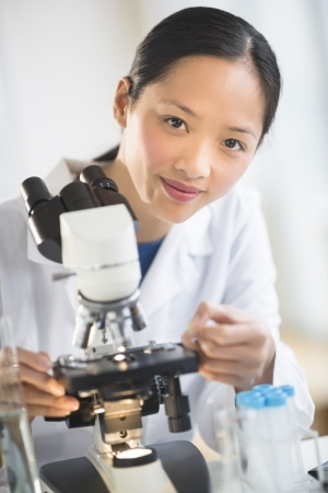 Portrait of confident mid adult female scientist smiling while using microscope in laboratory