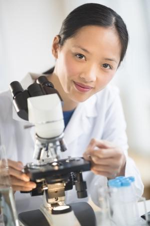 investigador cientifico: Retrato de confianza mediados científico hembra adulta que sonríe mientras que usa el microscopio en el laboratorio