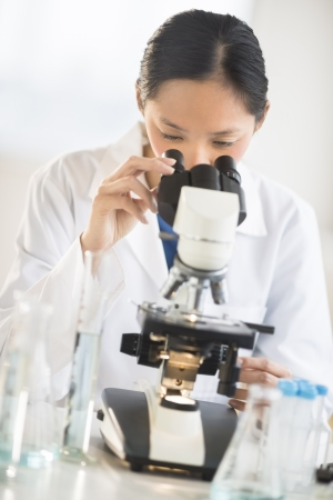 Mid adult Asian female scientist using microscope at desk in laboratory Standard-Bild