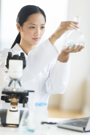 mid adult female: Mid adult female scientist analyzing chemical solution in flask at laboratory
