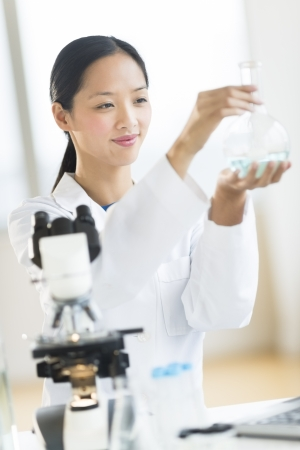 mid adult female: Mid adult female scientist smiling while analyzing chemical solution in flask at laboratory Stock Photo