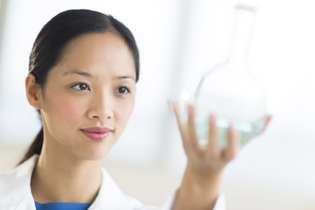 Close-up of mid adult female scientist analyzing chemical solution in flask at laboratory Фото со стока