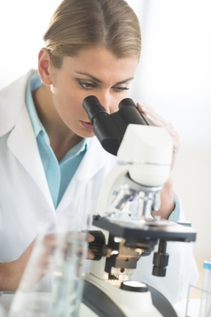 Young Caucasian female doctor using microscope at desk in laboratory photo