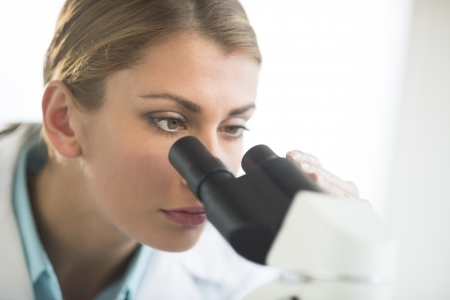 Close-up of young Caucasian female scientist using microscope in laboratory Stock Photo - 22118083