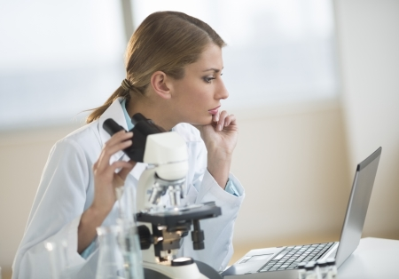 Young Caucasian female scientist looking at laptop while sitting with microscope at desk in laboratory photo