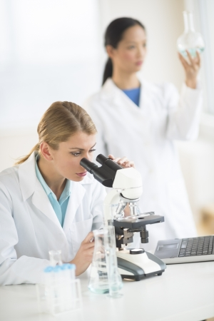 Young female scientist using microscope while colleague analyzing chemical solution in background Stock Photo - 22143683