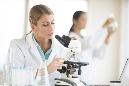 Young female scientist using microscope while colleague working in background photo