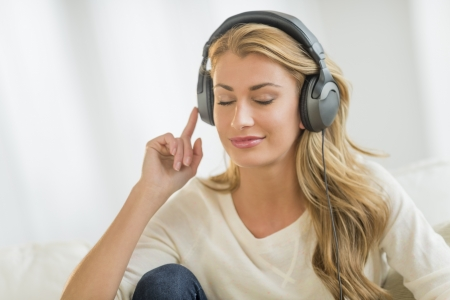 Beautiful young woman with eyes closed listening to music through headphones at home photo