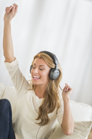 Happy young woman with hand raised enjoying music through headphones while sitting on sofa at home photo