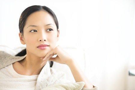 one mid adult woman only: Thoughtful young Asian woman with hand on chin looking away while relaxing at home