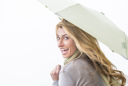 Portrait of cheerful young woman looking over shoulder while holding umbrella isolated over white background photo