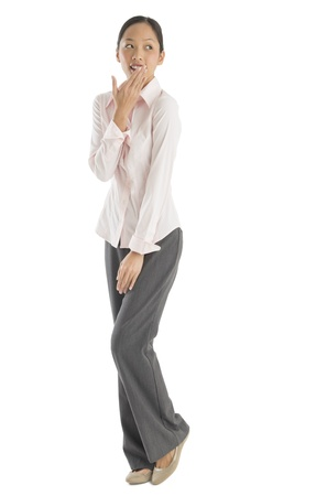 sideways glance: Full length of surprised mid adult businesswoman looking sideways while standing against white background Stock Photo