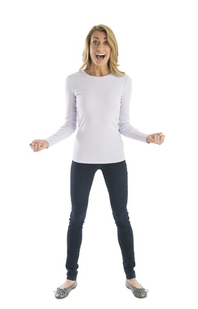 Portrait of excited young woman with clenched fists shouting while standing against white background