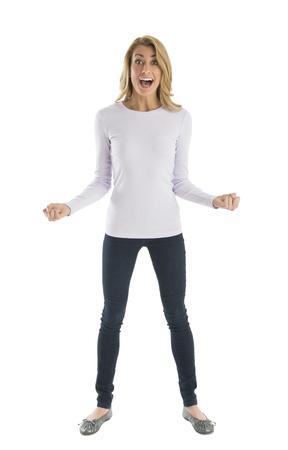 legs apart: Retrato de joven emocionada gritando con los pu�os cerrados mientras est� de pie contra el fondo blanco Foto de archivo