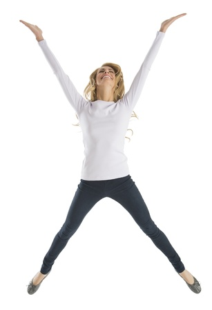 arms raised: Excited young Caucasian woman jumping isolated on white background