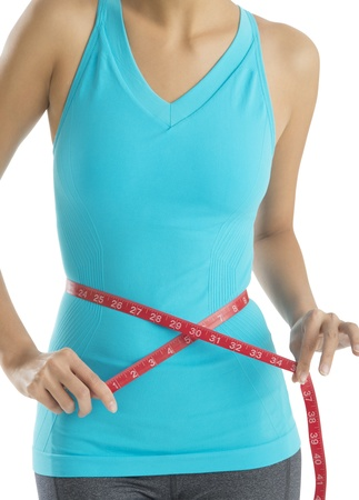 woman measuring: Midsection of woman with tape measure measuring her waistline isolated on white background Stock Photo