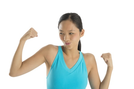 puckering lips: Happy mid adult woman puckering lips while flexing her muscles isolated on white background
