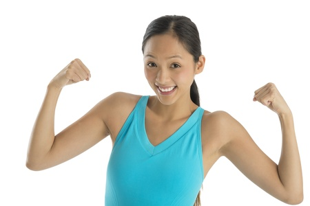 Portrait of cheerful mid adult woman in sports clothing flexing her arms against white background photo