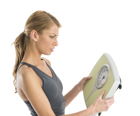 Worried young woman in sports clothing looking at weight scale against white background photo
