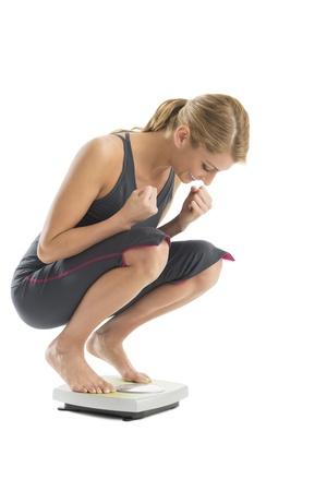 mujer cuerpo completo: Mujer joven emocionada con los pu�os cerrados que se pesa en escala del peso contra el fondo blanco Foto de archivo