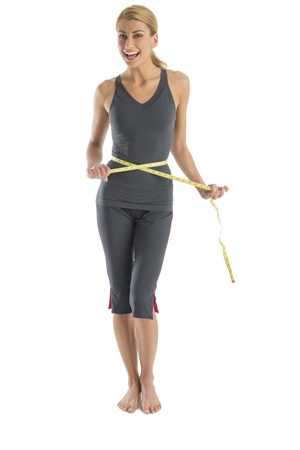 Portrait of cheerful young Caucasian woman holding tape measure around waist against white background