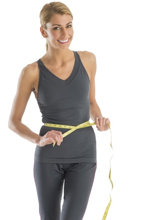 Portrait of happy young Caucasian woman measuring her waistline against white background