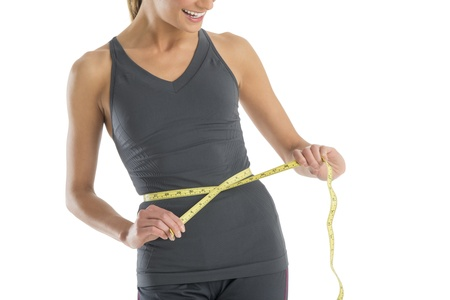 Midsection of young Caucasian woman smiling while measuring her waistline against white background
