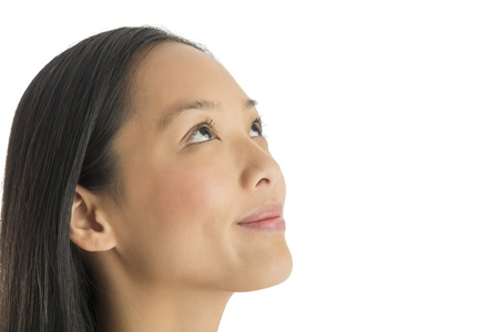 Close-up of thoughtful mid adult woman smiling while looking up against white background