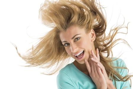 cabello rubio: Retrato de la alegre mujer rubia joven que sacude el pelo aislado en el fondo blanco