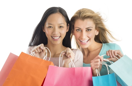 Portrait of happy shopaholic female friends carrying shopping bags against white background photo