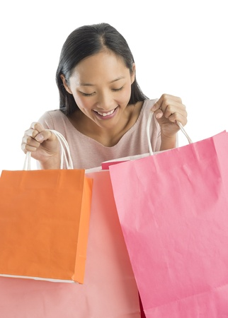 Excited mid adult Asian woman looking into shopping bags against white background photo