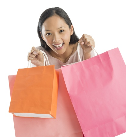 Portrait of excited mid adult Asian woman carrying shopping bags against white background photo