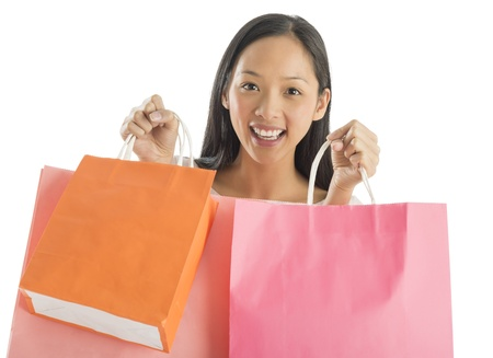 Portrait of shopaholic mid adult woman carrying shopping bags against white background photo