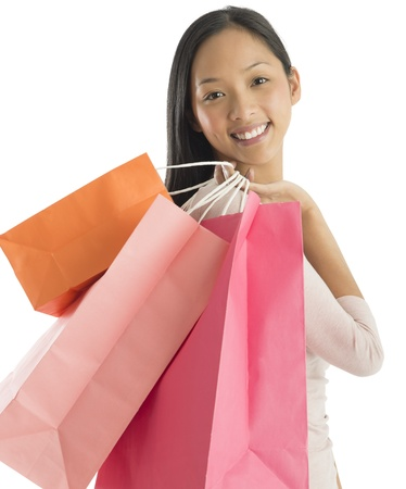 Portrait of beautiful mid adult woman carrying shopping bags against white background photo