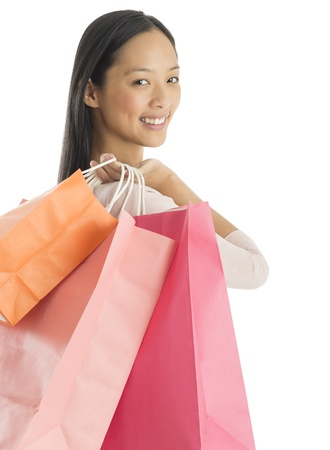 Portrait of beautiful shopaholic woman carrying shopping bags against white background photo