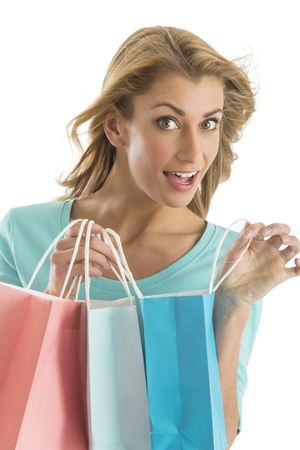 Portrait of excited young woman carrying shopping bags isolated over white background photo