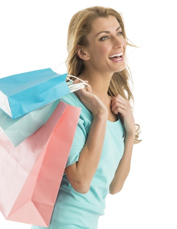 Happy young Caucasian woman looking away while carrying shopping bags against white background photo