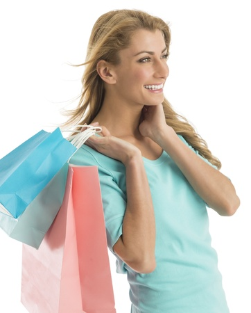 Happy young shopaholic woman looking away while carrying shopping bags against white background photo