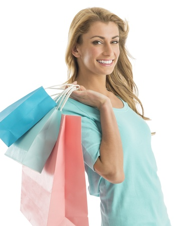 Portrait of happy young shopaholic woman carrying shopping bags isolated over white background photo
