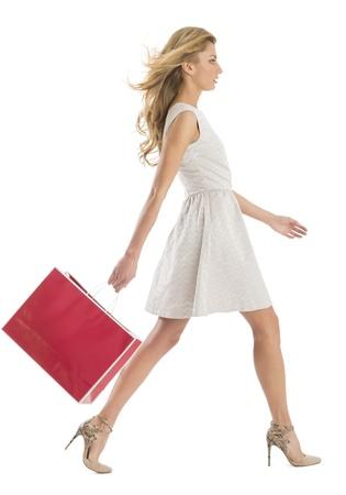 白い背景で隔離されたショッピング バッグで歩く若い女性の完全な長さの側面図