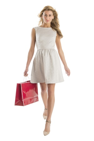 Front view portrait of young woman walking with shopping bag isolated over white background Standard-Bild