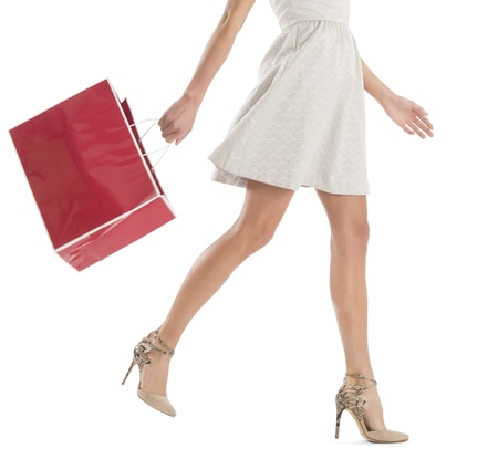 paper bag: Low section of young woman walking with shopping bag isolated over white background