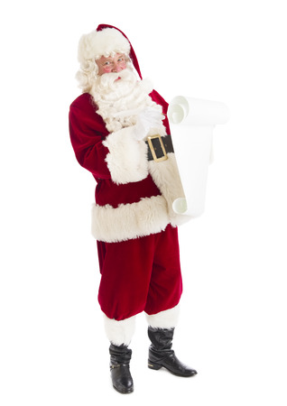 Portrait of Santa Claus preparing list while standing isolated over white background photo