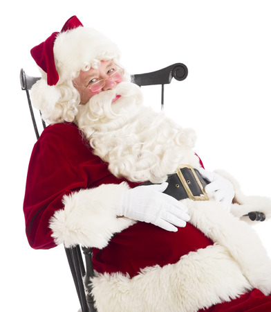 Portrait of Santa Claus with hands on stomach sitting on chair isolated over white background photo