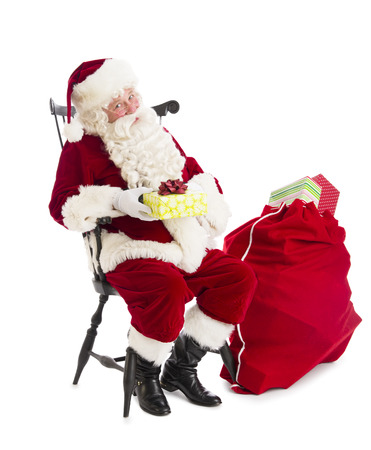 Portrait of Santa Claus holding gift box while sitting on chair by bag isolated over white background photo