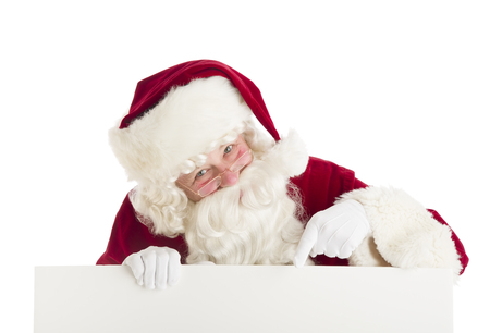 Portrait of Santa Claus pointing at blank sign against white background