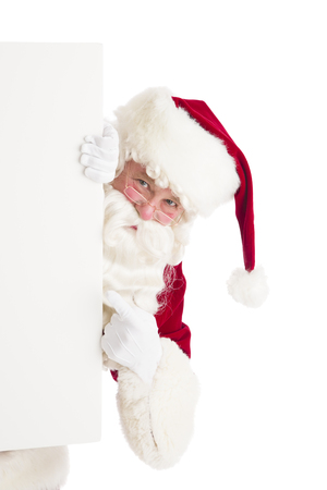 Portrait of Santa Claus pointing at blank sign against over white background