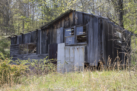 An Abandoned Shack sits in tall grass Stock Photo