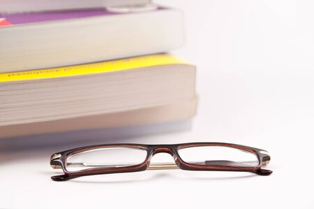 Folded glasses next to stack of books Stock Photo