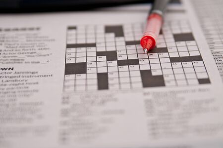 passtime: Newspaper crossword puzzle and red pen